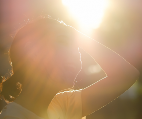 žena sa drží za hlavu a svieti na ňu slnko