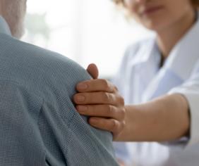 Lekárka drží pacienta za rameno